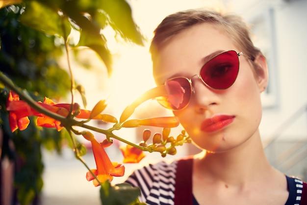 屋外の花とサングラスの茂みを身に着けているきれいな女性