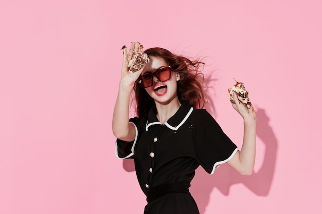 Pretty woman wearing sunglasses cake in hands enjoyment pink background