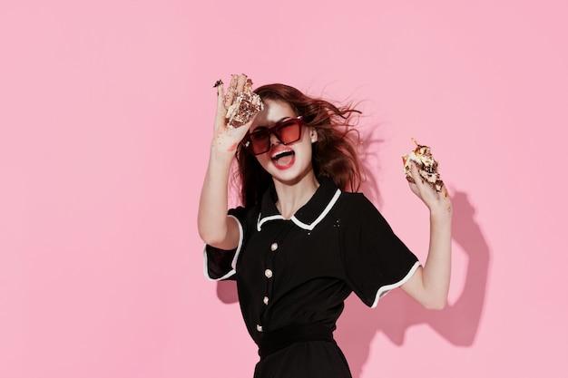 手でサングラスケーキを身に着けているきれいな女性の楽しみピンクの背景