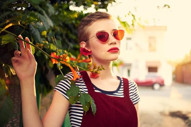 サングラスをかけているきれいな女性屋外の花の装飾ポーズ
