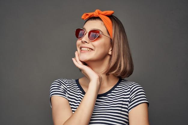 モダンなスタイルでファッションをポーズサングラスをかけているきれいな女性
