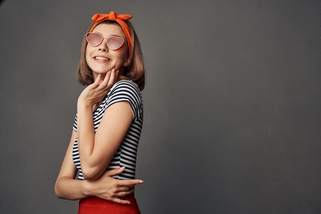 モダンなスタイルでファッションをポーズサングラスを着ているきれいな女性