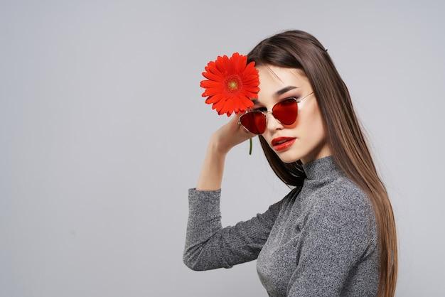 サングラスをかけているきれいな女性赤い花赤い唇の贅沢