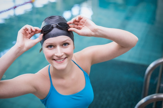 Pretty woman wearing swim cap and swimming goggles at the pool
