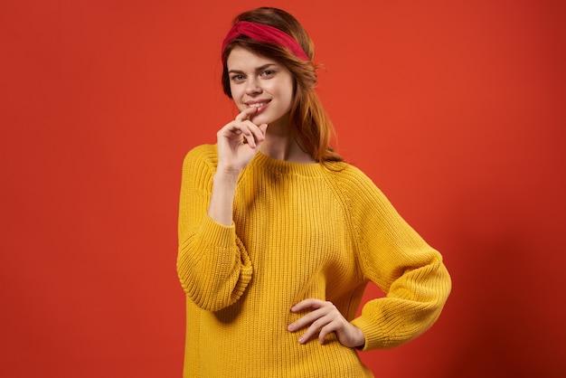 黄色いセーター赤いヘッドバンドヒッピーストリートスタイルの赤い壁を身に着けているきれいな女性。