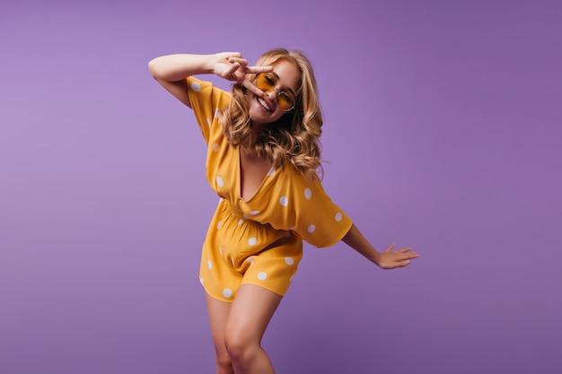 예쁜 여자는 주황색 드레스와 밝은 미소로 춤을 추는 노란색 선글라스를 착용합니다. 물결 모양의 머리가 재미와 화려한 여자의 실내 초상화.
