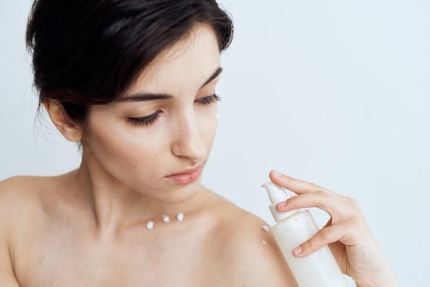 Красивая женщина носит косметику по уходу за кожей