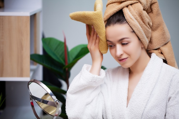 Pretty woman in white coat wipes face with towel after shower