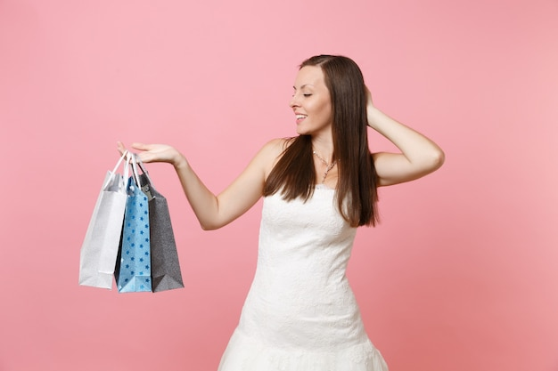 Pretty woman in white dress keeping hand on head looking on multi colored packages bags with purchases after shopping