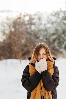 Pretty woman in winter clothes warming hands
