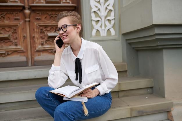コミュニケーションを読んで屋外で彼の手に本を持つきれいな女性