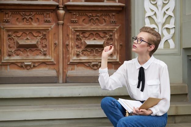 教育を読んで屋外で彼の手に本を持つきれいな女性