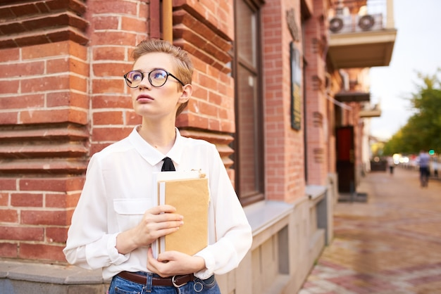 ライフスタイルを読んで屋外で本を手に持っているきれいな女性