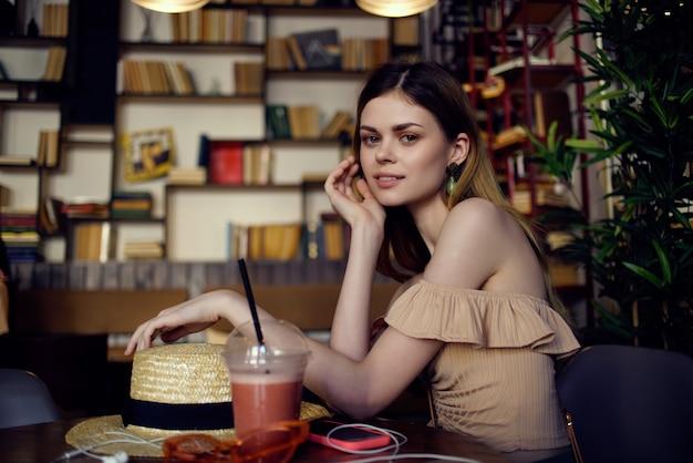 カフェファッションの手に本を持つきれいな女性