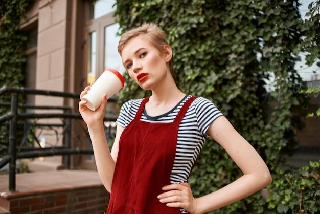 茂みの近くの通りで一杯の飲み物を持つきれいな女性