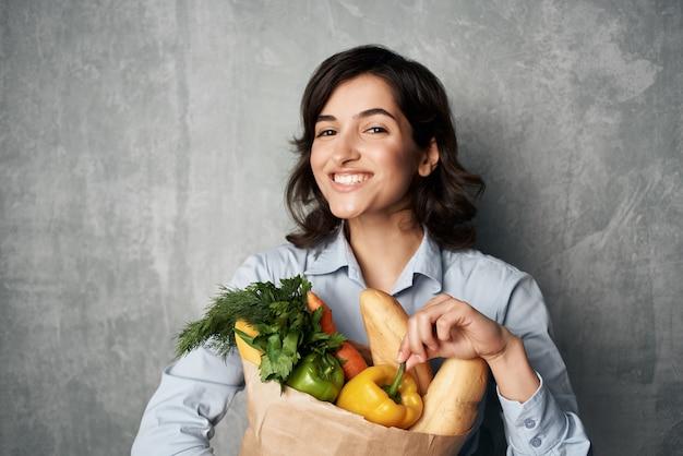 Красивая женщина с пакетом покупок доставки овощей бакалеи. фото высокого качества
