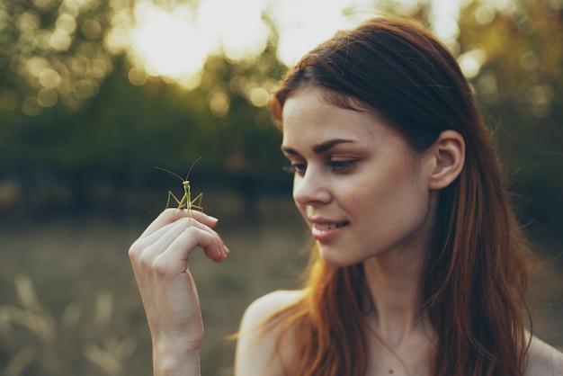 手にカマキリの野生の自然を持つきれいな女性