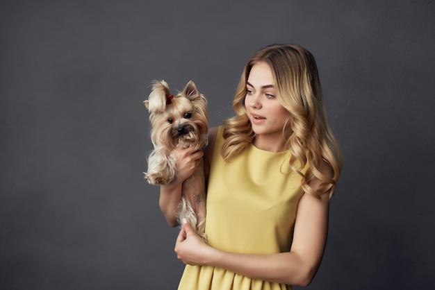 トリミングされたビューのファッションをポーズする小さな犬のメイクできれいな女性
