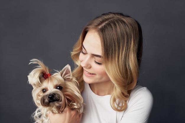 トリミングされたビューをポーズする小さな犬のメイクアップを持つきれいな女性