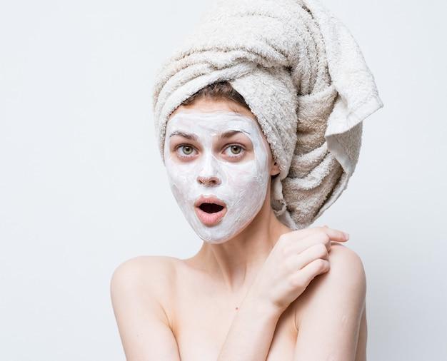 Красивая женщина с полотенцем на голове и белой маской на фоне черных точек на лице
