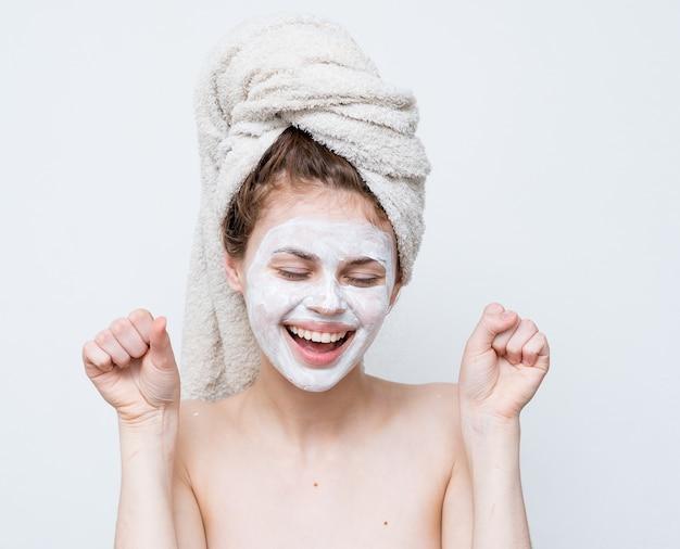 Красивая женщина с полотенцем на голове маска для лица обнаженные плечи привлекательный вид.