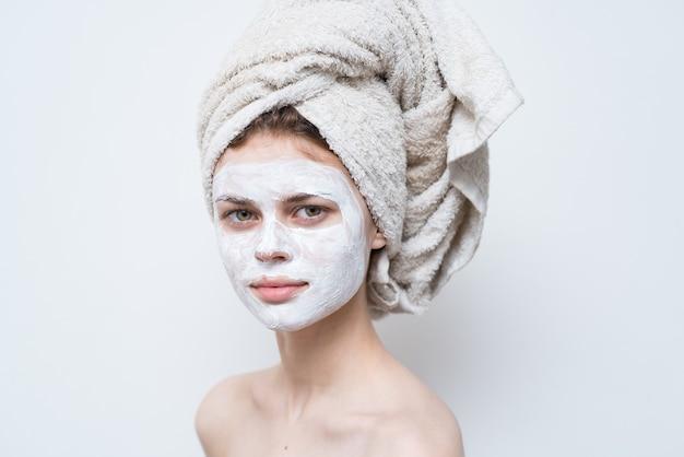 Красивая женщина с полотенцем на голове, маска для лица, обнаженные плечи, привлекательный вид