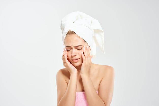顔のスタジオのクローズアップで私の頭のにきびにタオルを持ったきれいな女性。高品質の写真