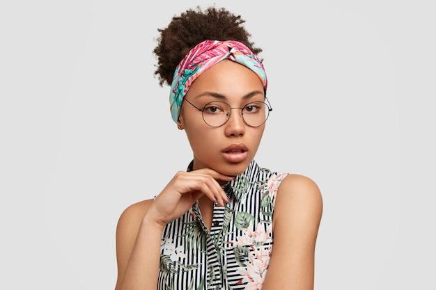 Bella donna con acconciatura afro, guarda seriamente e misteriosa davanti alla telecamera, si sente sicura o sicura di sé