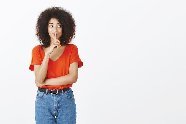 Красивая женщина с афро прической позирует в студии