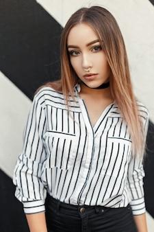 Красивая женщина с серьгой в носу в стильной полосатой блузке у стены