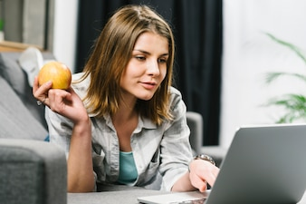 Pretty woman with apple browsing laptop