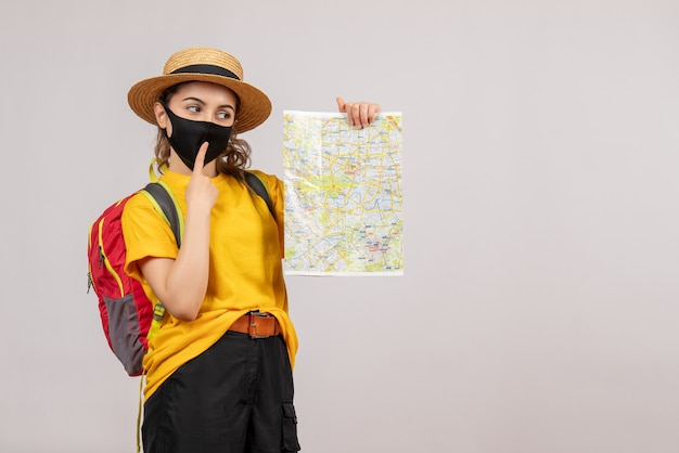 Bella donna con zaino che sorregge mappa su grigio