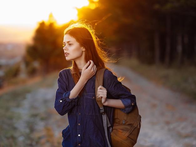 森の散歩風景の自由のバックパックを持つきれいな女性