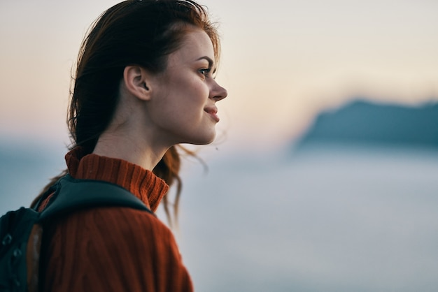 Красивая женщина с рюкзаком путешествует по горам на свежем воздухе с копией пространства