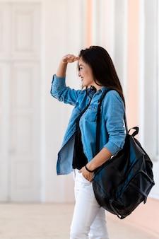 배낭과 예쁜 여자입니다. 파란색 셔츠와 흰색 청바지를 입은 젊은 여성의 모습. 눈 근처에 손으로 측면을 찾고 있습니다. 측면에서 봅니다. 반쪽 얼굴보기.