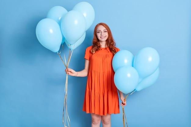 エレガントなドレスを着て、風船を持ったきれいな女性は、赤いウェーブのかかった髪をしています