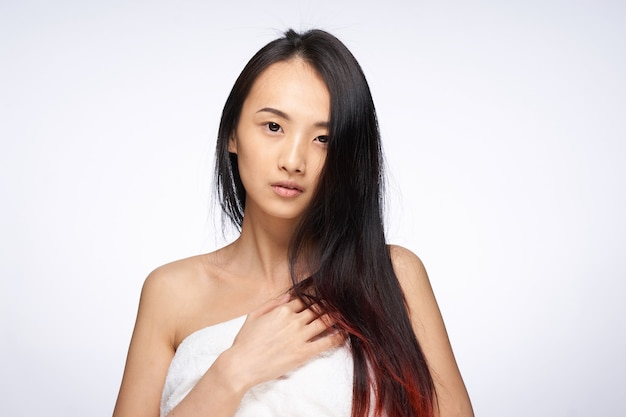 シャワーの緩い髪の光の後に裸の肩を持つきれいな女性