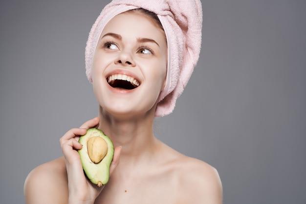 裸の肩を持つきれいな女性アボカドビタミンフルーツエキゾチック