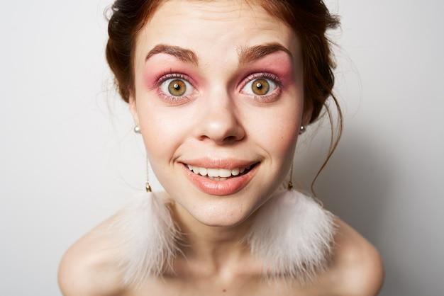Красивая женщина с открытыми плечами яркий макияж пушистые серьги косметика гламур
