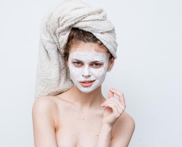 Красивая женщина с обнаженными плечами очаровывает маску для лица с чистой кожей. фото высокого качества