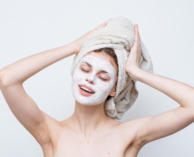 裸の肩のクリームマスクスキンケアクロップドビューのきれいな女性。