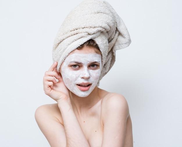 Красивая женщина с голыми плечами лицо крем полотенце на чистой коже головы