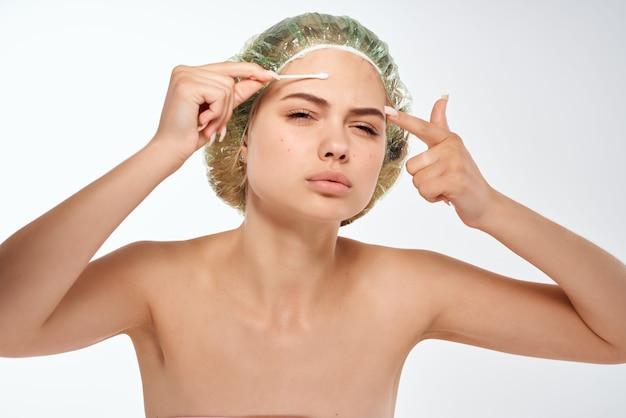裸の肩の顔の化粧品を持つきれいな女性