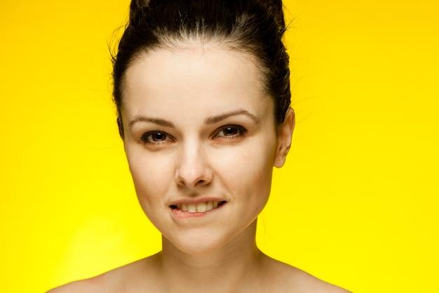 裸の肩を持つきれいな女性が髪を集めた透明な肌黄色の背景