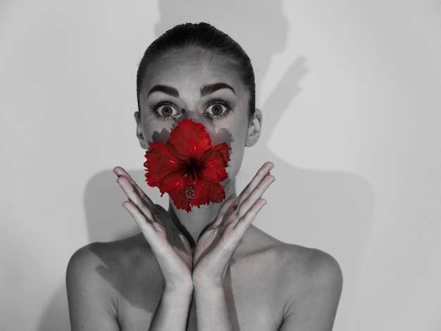Pretty woman with bare shoulders holding flower in mouth cropped view gray photo. high quality photo