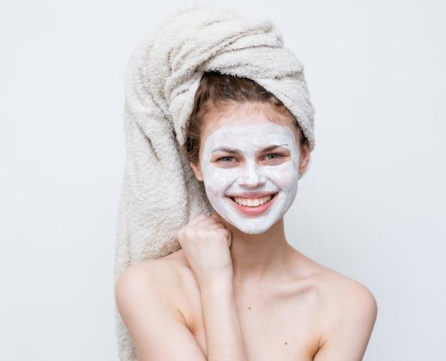 頭のフェイスマスクのスキンケアのクローズアップに裸の肩のタオルを持つきれいな女性。