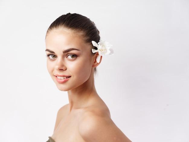 裸の肩の白い花のクローズアップときれいな女性
