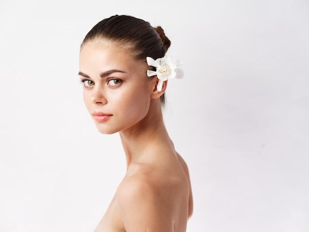 裸の肩を持つきれいな女性髪の化粧品の孤立した背景の白い花