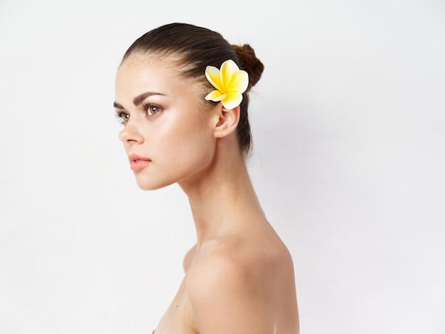Красивая женщина с обнаженными плечами, желтый цветок за ухом, очарование чистой кожи