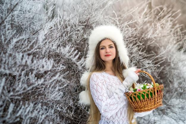 Красивая женщина с корзинами и белым свитером, меховой шапкой в зимнем снежном парке